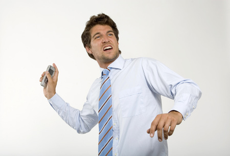 Young Businessman Throwing Mobile Phone,Close-Up LANG_EVOIMAGES