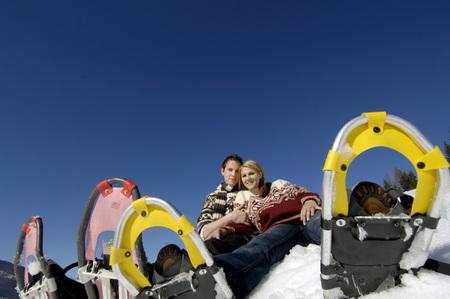Young Couple Sitting In Snow With Snow Shoes, Low Angle View