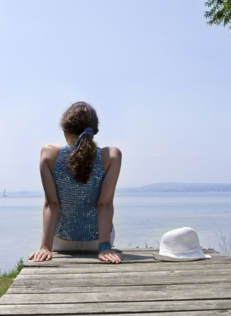 Young Woman Sitting On Jetty, Rear View