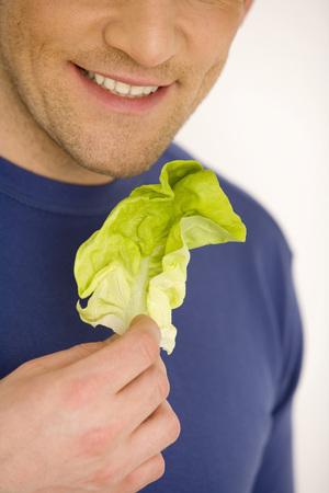 Young Man Holding Lettuce Leaf, Smiling, Close-Up