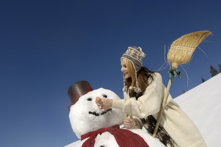 Young Woman Making Snowman, Smiling, Low Angle View LANG_EVOIMAGES