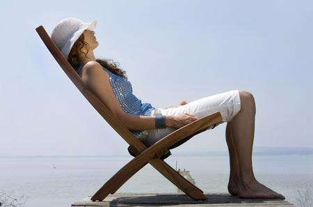 Young Woman Sitting On Deck Chair On Jetty, Side View