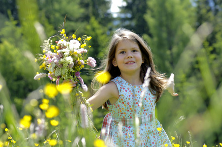 Girl (6-7) With Bunch Of Flowers In Meadow,Smiling,Close-Up