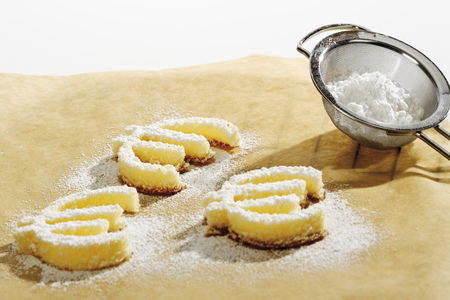 Cookies Formed As Euro Signes On Baking Paper, Close-Up LANG_EVOIMAGES