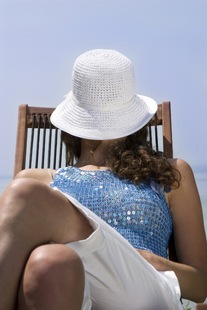 Young Woman Sitting On Deck Chair On Jetty, Close-Up