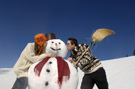 Young Couple Kissing Snow Man, Low Angle View