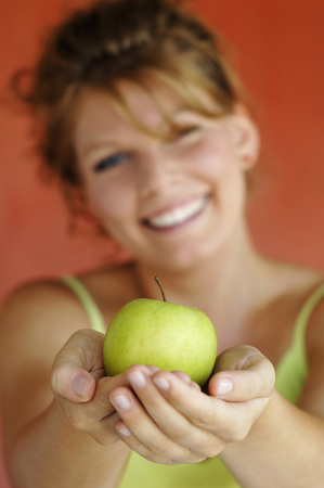 Young Woman Holding Apple, Close-Up
