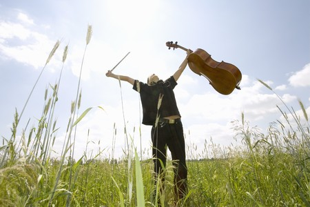 Young Man Standing In Field With Cello,Low Angle View