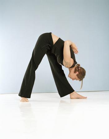 Young Woman Doing Yoga,Performing Prasarita Padottanasana LANG_EVOIMAGES