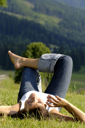 Woman Lying In Field Using Mobile Phone