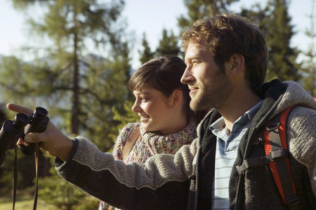 Young Couple In Mountains, Man Holding Binocular LANG_EVOIMAGES