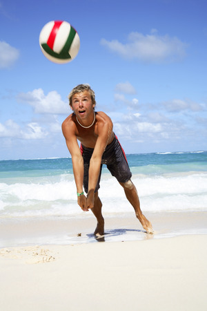 Young Man Playing Volley Ball On Beach