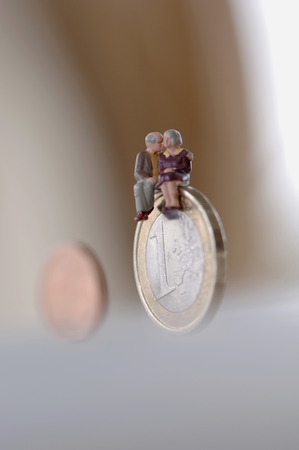 Senior Couple Sitting On Coin, Close-Up