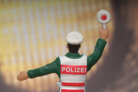 Police Figurine In Front Of Automobile Headlight LANG_EVOIMAGES