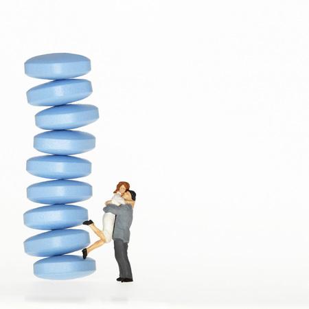 Man Embracing Woman Next To Pile Of Pills