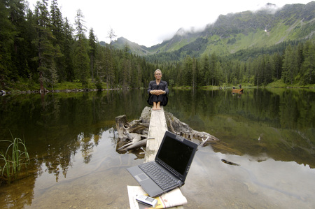 Businesswoman Sitting At Lake, Laptop In Foreground LANG_EVOIMAGES