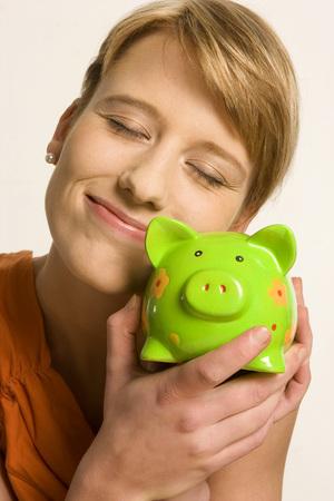 Young Woman Embracing Piggy Bank, Close-Up