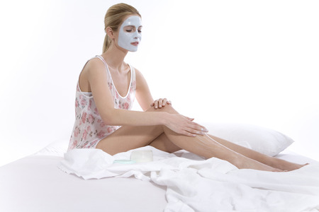 Woman With Beauty Mask On Face, Sitting On Bed LANG_EVOIMAGES