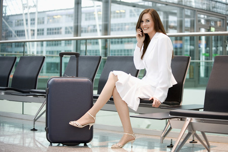 Business Woman Sitting In Airport Lounge, Using Mobile Phone, Smiling, Portrait