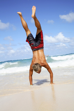 Young Man Making Handstand On Beach LANG_EVOIMAGES