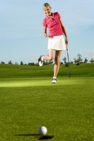 Joven mujer jugando al golf