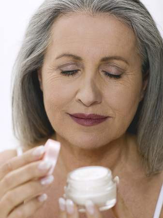 cremas faciales: Senior Woman Opening Cream Pot LANG_EVOIMAGES