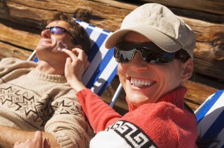 Austria, Salzburger Land, Couple Sitting In Front Of Hut LANG_EVOIMAGES