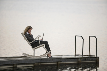 technolgy: Businesswoman Sitting In Rocking Chair On Jetty, Using Laptop, Side View LANG_EVOIMAGES