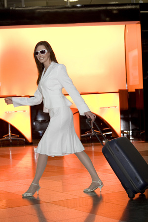 front facing: Business Woman Pulling Suitcase, Smiling, Side View LANG_EVOIMAGES
