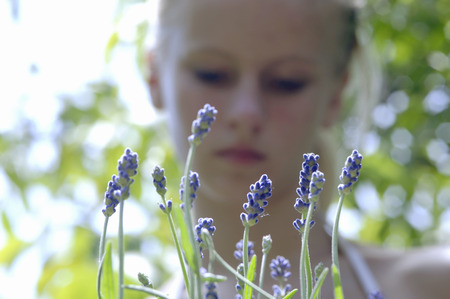 Young Woman Standing In Lavender Field, Focus On Lavender Flowers At Foreground, Close-Up