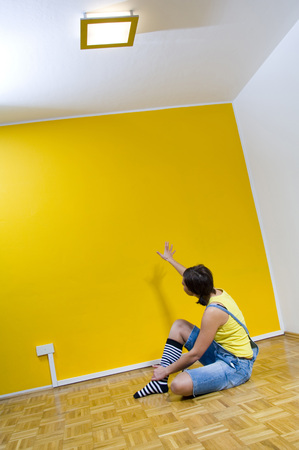 Woman Sitting On Floor, Looking At Yellow Wall LANG_EVOIMAGES