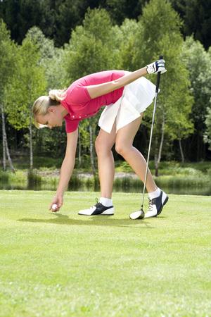 Junge Frau, die Golfball platziert