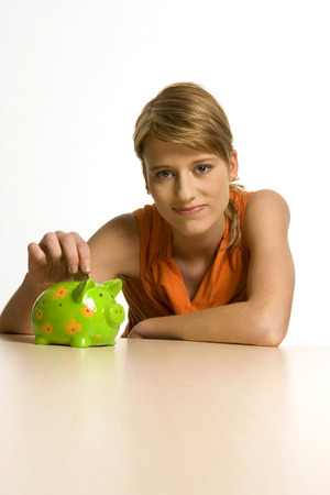 Young Woman With Green Piggy Bank, Portrait LANG_EVOIMAGES