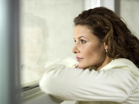 Businesswoman Looking Out Of Window LANG_EVOIMAGES