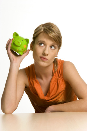 Young Woman Holding Piggy Bank, Looking Up, Close-Up