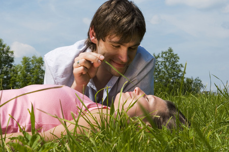 closed community: Young Couple In Meadow, Man Holding Blade Of Grass, Close-Up LANG_EVOIMAGES