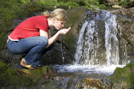 cowering: Young Woman Drinking Water From Stream, Side View LANG_EVOIMAGES