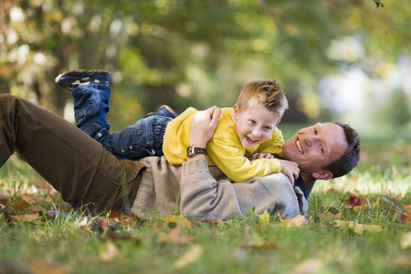 Father Playing With Son In Meadow, Side View
