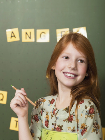Girl Standing In Front Of Blackboard, Holding Pencil