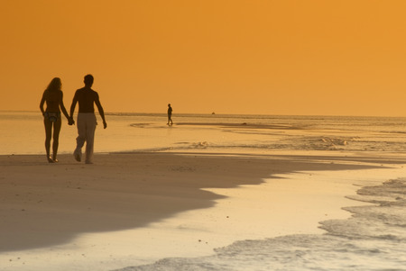 Couple On The Beach, Silhouetted At Sunset, Maldives