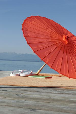 Germany, Bavaria, Lake Starnberg, Parasol And Bathing Shoes On Jetty