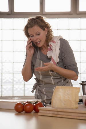 Mature Woman In Kitchen, Using Mobile Phone