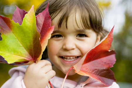 Girl (4-5) Holding Autumn Leaves, Close-Up