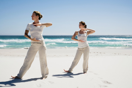 Two Women Exercising Yoga On Beach LANG_EVOIMAGES