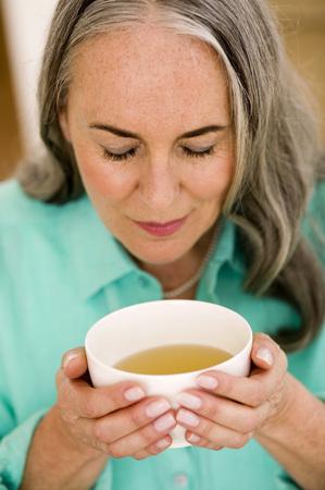 Mature Woman Holding Cup Of Tea, Portrait, Close-Up LANG_EVOIMAGES