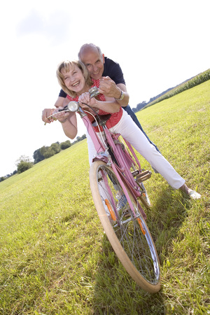 Mature Couple Riding Bike LANG_EVOIMAGES