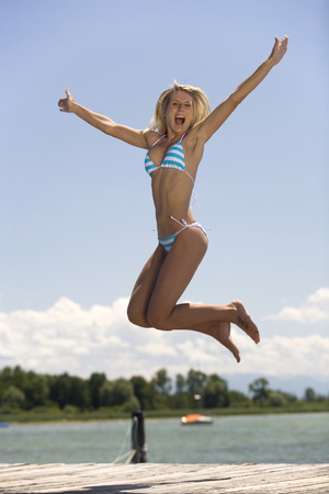 Young Woman Jumping On Jetty LANG_EVOIMAGES
