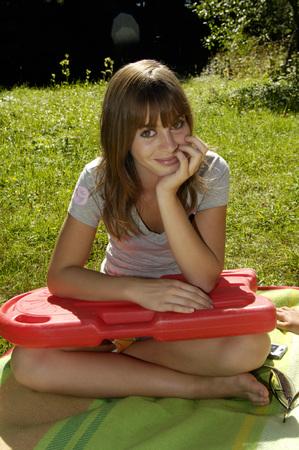 Teenage Girl (16-17) Sitting In Meadow, Holding Float