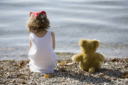edge: Germany, Bavaria, Ammersee, Little Girl (3-4) Sitting On Beach, Rear View LANG_EVOIMAGES