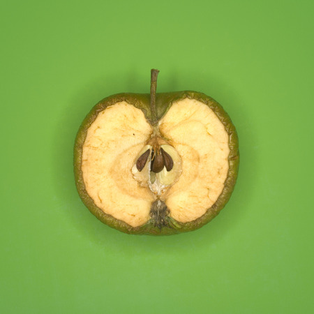 disgusted: Rotting Green Apple Cut In Half, Elevated View LANG_EVOIMAGES